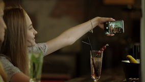 Women taking selfie. Two young women taking selfie on a phone sitting in a bar stock footage