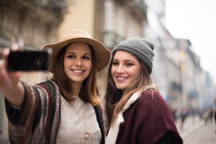 Women taking selfies. Trendy young women taking selfies in the city Royalty Free Stock Images