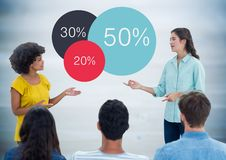 Women talking before audience against colourful statistics blurry blue wood panel Royalty Free Stock Images