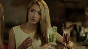 Women talking at a bar counter. Two young beautiful women with cocktails talking at a bar counter stock video