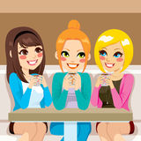 Women Talking At Coffee Shop. Three beautiful women talking friendly at coffee shop while drinking hot beverages Royalty Free Stock Photos