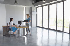 Women Talking At Desk In Empty Office royalty free stock image
