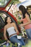 Women talking in garden centre at open car trunk Stock Photo