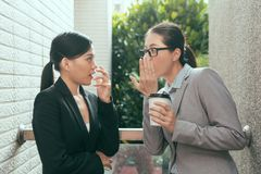 Women talking about office gossip. Two beautiful Asian women talking about office gossip and feel shocked at rest time outdoor of the studio stock photos