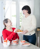 Women talking over coffee in   kitchen. Two mature women talking at   kitchen table with   cup of tea Royalty Free Stock Photos
