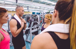 Women talking with personal trainer after training. Group of women friends talking with personal trainer of a fitness center after hard training day Stock Images