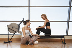 Women Talking At Rowing Machine In Health Club Stock Image