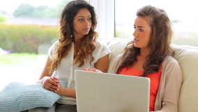 Women talking on sofa. With laptop stock footage