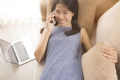 Women are talking on the sofas. She has a mac book. royalty free stock photography