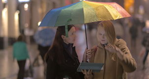 Women talking on the street on rainy day. Two young women with umbrella stand talking and gesticulating cheerfully on the street on rainy day, they watch stock video footage