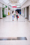 Women talking to each other while walking in shopping mall Royalty Free Stock Photography