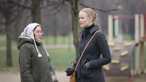 Women talking. Two women talking outdoor. Friends or neighbours having conversation stock video footage