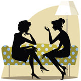Women talking. Two women talking on the sofa Stock Photos