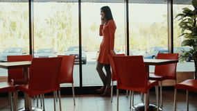 Women talks on the phone near the window in cafe. in full growth stock video