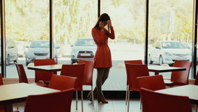 Women talks on the phone near the window in cafe. in full growth stock video footage