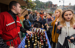 Women tasting wine with bartender in national georgian costume at festival Royalty Free Stock Image