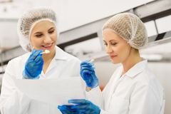 Women technologists tasting ice cream at factory. Food production, industry and people concept - happy women technologists with clipboard tasting ice cream Royalty Free Stock Photo