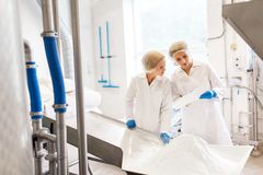 Women technologists working at ice cream factory. Manufacture, industry, food production and people concept - women technologists with paper and powdered milk at stock photos