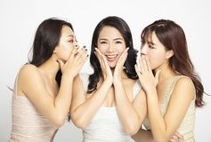Women telling whispering and secret gossip. Three women telling whispering and secret gossip royalty free stock photos