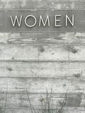 Women Text. The word, `Women` in modern font on a wooden background wall. Faded saturation of color. Outdoor wall shows the plants at the bottom creating a frame Stock Photos