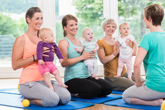 Women and their babies in mother-child gymnastic course stock image