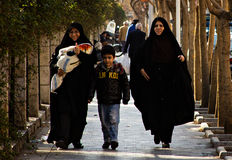 Women in Theran, Iran. Two women and a child walk in a street of Tehran, the capital of Iran, dressing their typical black suit, called chador royalty free stock image