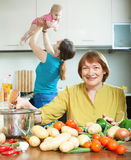 Women of three generations in domestic kitchen Stock Photos