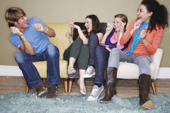 Women Throwing Popcorn At Male Friend Royalty Free Stock Photography