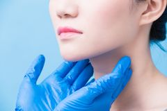 Women with thyroid gland problem. On the blue background stock photos