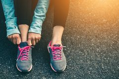 Women tied up the shoe laces prepare to run. Royalty Free Stock Images