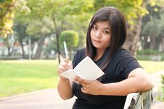 Women are to sit and write books. Women sitting in the park and is writing a notebook in it Royalty Free Stock Photos