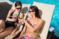 Women toasting drinks by swimming pool Stock Photography