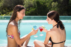 Women toasting drinks by swimming pool Royalty Free Stock Images