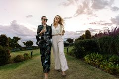 Women together with a glass of wine. Two young women walking together in lawn with a glass of wine. Best friends with wine having fun outdoors Stock Image