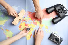 Women with tourist items planning vacation on world map. Travel agency. Women with tourist items planning vacation on world map, top view. Travel agency royalty free stock photos