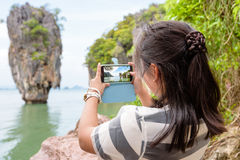 Women tourist shooting natural view by mobile phone. Women tourist he is shooting a beautiful scenic view by mobile phone at Khao Tapu or James Bond Island in Ao Stock Images