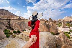 Free Women Tourists Holding Man`s Hand And Leading Him To Fairy Chimneys In Cappadocia, Turkey. Royalty Free Stock Photo - 166868305