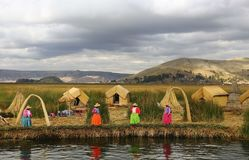 Women in traditional attires on Uros Islands lake Titicaca stock photo