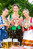 Women in traditional Bavarian clothes in beergarden. Young women in traditional Bavarian clothes or tracht with a gingerbread souvenir heart in beergarden on Stock Photography