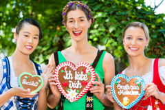 Women in traditional Bavarian clothes in beergarden. Young women in traditional Bavarian clothes or tracht with a gingerbread souvenir heart in beergarden on Stock Photos