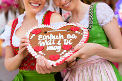 Women in traditional Bavarian clothes on festival. Young women in traditional Bavarian clothes - dirndl or tracht -with a gingerbread souvenir heart on a Royalty Free Stock Photos