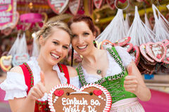 Women in traditional Bavarian clothes on festival. Young women in traditional Bavarian clothes - dirndl or tracht -with a gingerbread souvenir heart on a Stock Photography