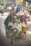 Saigon, Vietnam - June 2017: Women in conical hats bargaining on street market, Saigon, Vietnam. Women in traditional conical hats bargaining on busy asia Royalty Free Stock Photo