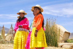Women in traditional dresses. PUNO, PERU - NOV 28: Unidentified women in traditional dresses welcome tourists in Uros Island, Puno, Peru, NOV. 28. 2010. The Uros stock image