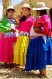 Women in traditional dresses. PUNO, PERU - NOV 28: Unidentified women in traditional dresses welcome tourists in Uros Island, Puno, Peru, NOV. 28. 2010.The Uros royalty free stock images