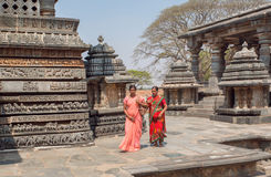 Women in traditional indian sari going to ancient Hindu temple Hoysaleshwara with murble carvings Stock Images