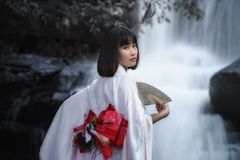 Women in traditional japanese kimono. With waterfall,young pretty geisha in kimono Royalty Free Stock Photography