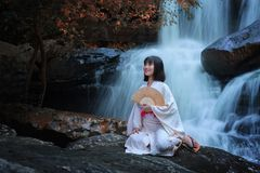 Women in traditional japanese kimono. With waterfall,young pretty geisha in kimono Stock Photo