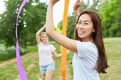 Women train coordination with ribbons. Two women play with colorful ribbons and train coordination in nature royalty free stock images