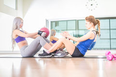 Women training abs in a gym. Two sportive women training abs with weighted ball in a gym - Girls working out to shape their body Royalty Free Stock Photography